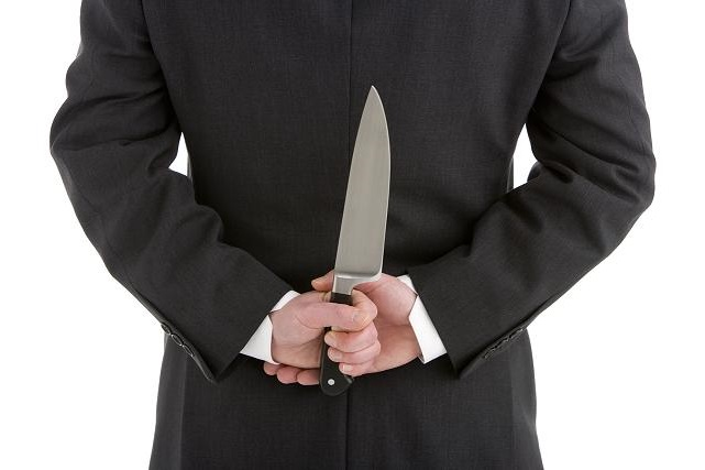 Businessman Holding Knife Behind His Back